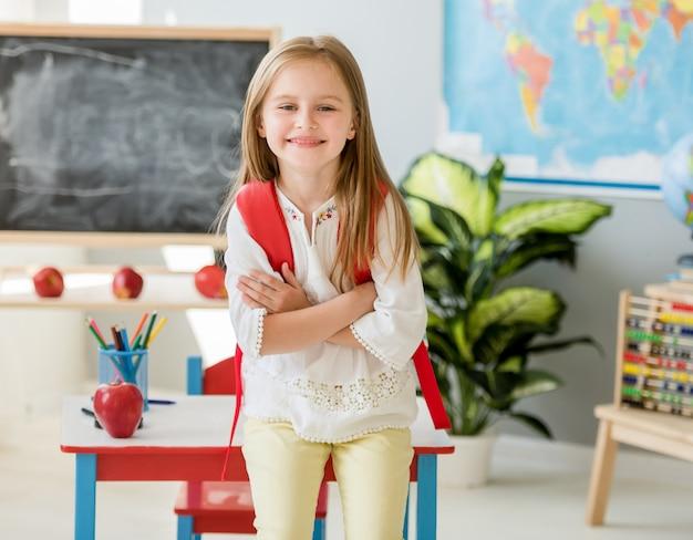 Petite fille blonde souriante debout près du bureau avec son sac rouge dans la classe de l'école spacieuse