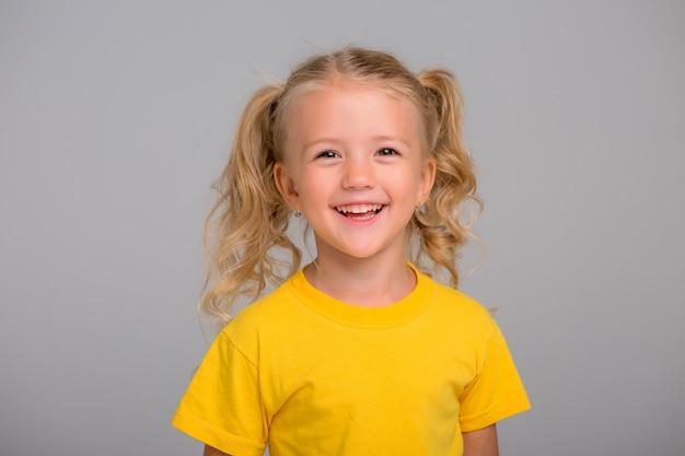 Petite fille blonde souriante sur fond clair