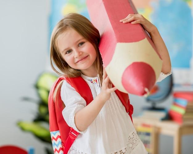 Petite fille blonde souriante avec sac rd tenant un énorme crayon décoratif rouge dans la classe de l'école