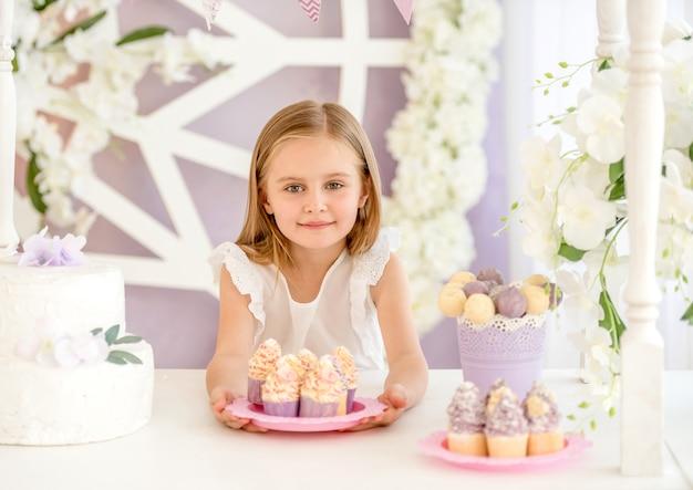 Petite fille blonde souriante tenant une assiette rose avec des bonbons sucrés sur le tableau blanc dans le bar à bonbons