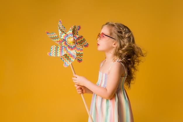 Petite fille blonde sourit dans une robe d'été, lunettes de soleil, tenant le moulin à vent d'un enfant sur un mur jaune