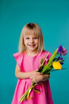 Petite fille blonde sourit dans une robe rose et tenant un bouquet de fleurs de printemps sur un espace bleu isoler