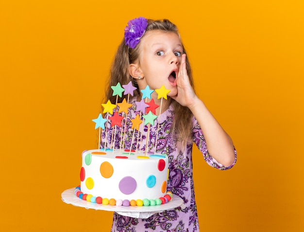 Petite fille blonde surprise tenant un gâteau d'anniversaire et gardant la main près de la bouche appelant quelqu'un isolé sur un mur orange avec espace de copie