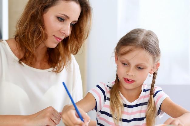 Petite fille blonde tenir au crayon de bras dessin quelque chose