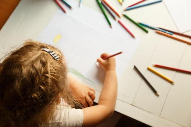 Petite fille blonde en train de peindre
