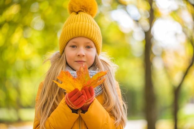 Petite fille blonde en vêtements jaunes avec feuille jaune, automne