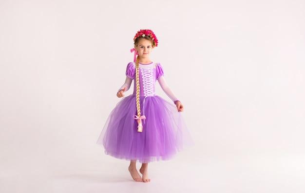 Petite fille blonde vêtue d'une robe de princesse fée violette sur fond blanc. déguisement enfant pour fête du nouvel an
