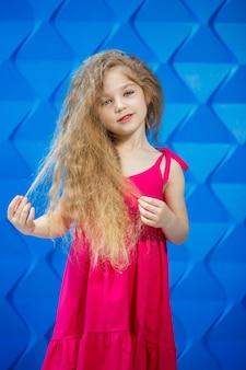 Petite fille blonde vêtue d'une robe rose sur fond bleu dansant et riant, émotions lumineuses de joie des enfants, enfance heureuse