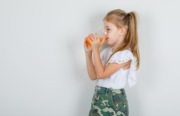 Petite fille, boire du jus et regarder ailleurs en t-shirt blanc