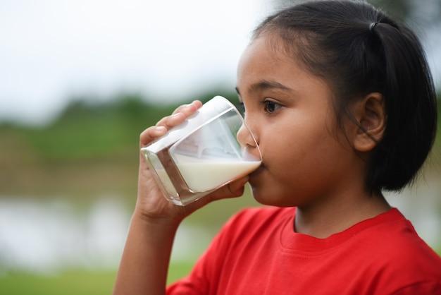 Petite fille à boire du lait dans le parc