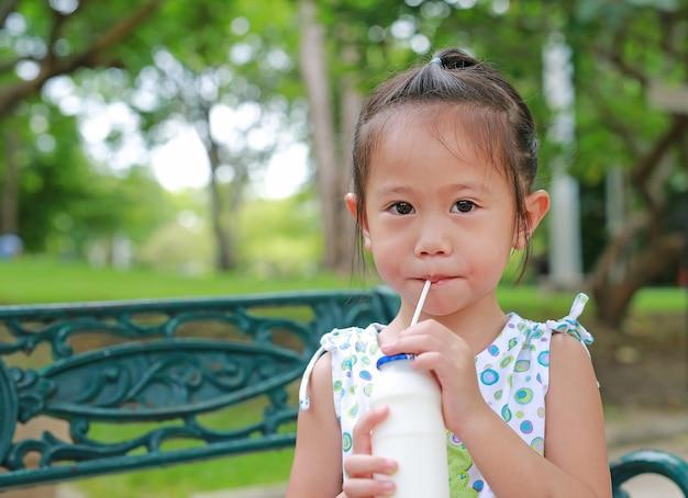 Petite fille, boire du lait avec de la paille dans le parc