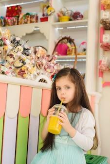 Petite fille, boire, jus orange, par, paille
