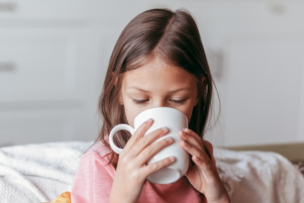 La petite fille boit dans une tasse blanche. portrait en gros plan