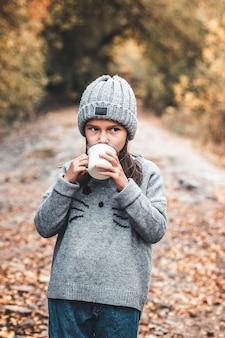 Petite fille boit du thé dans le parc d'automne