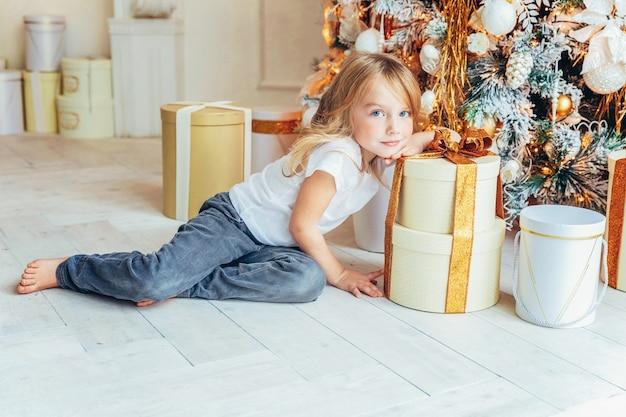 Petite fille avec boîte-cadeau près de l'arbre de noël