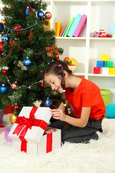 Petite fille avec une boîte présente près de l'arbre de noël