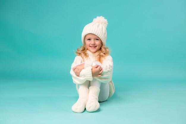 Petite fille en bonnet d'hiver blanc et pull sur bleu