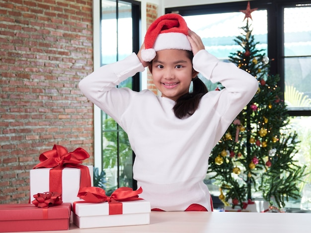 Petite fille en bonnet de noel avec des coffrets cadeaux à la maison.