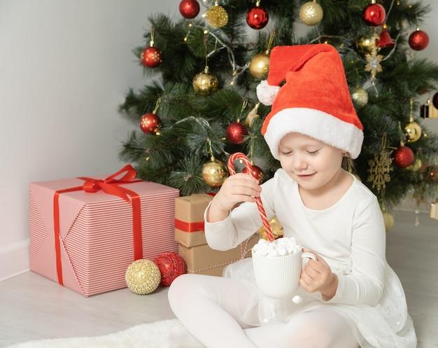 Petite fille en bonnet de noel tient une tasse de chocolat chaud ou de cacao avec guimauve près de l'arbre de noël