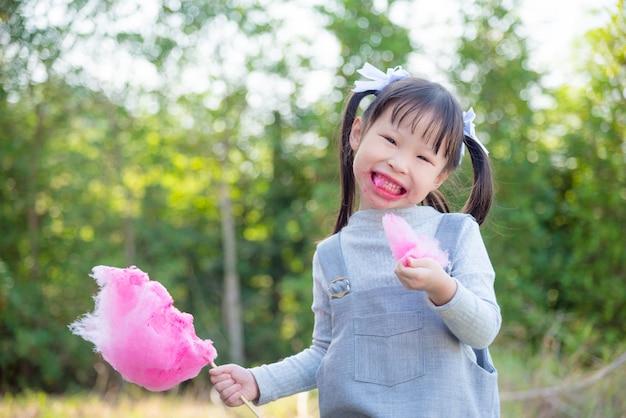 Petite fille avec la bouche sale en mangeant une barbe à papa rose