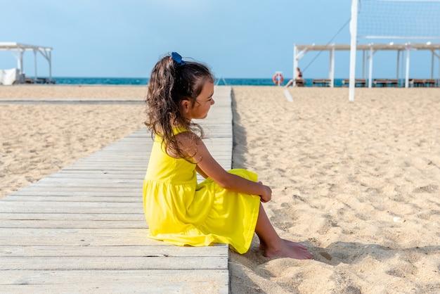 Petite fille bouclée dans une robe jaune est assise sur une plage déserte de sable lors d'une journée ensoleillée de vacances amusantes