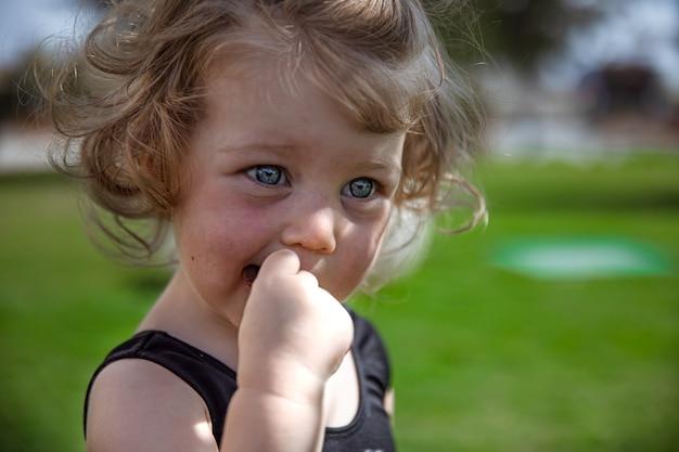 Petite fille bouclée en été en plein air gros plan sur fond flou