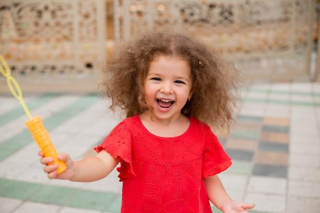 Petite fille bouclée laisse les bulles et se réjouit