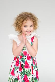 Petite fille bouclée souriant sur blanc