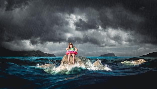 Petite fille avec bouée de sauvetage assise sur un rocher pendant une tempête.