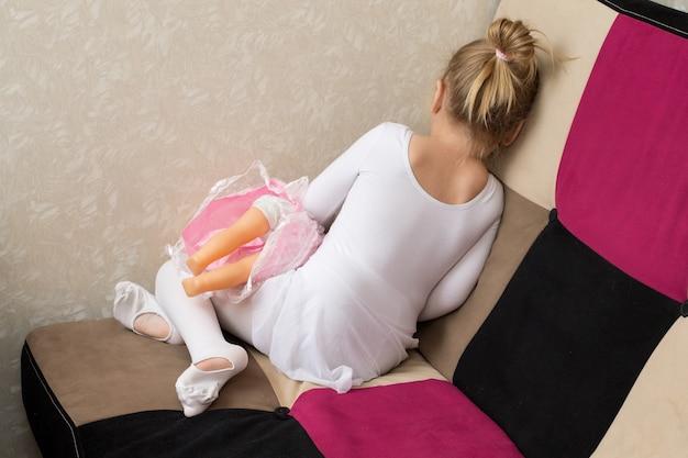 Petite fille bouleversée avec une poupée, vue arrière