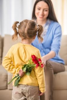 Petite fille avec bouquet de belles roses derrière le dos.