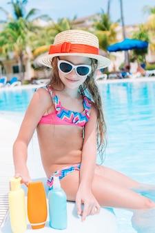 Petite fille avec une bouteille de crème solaire dans la piscine