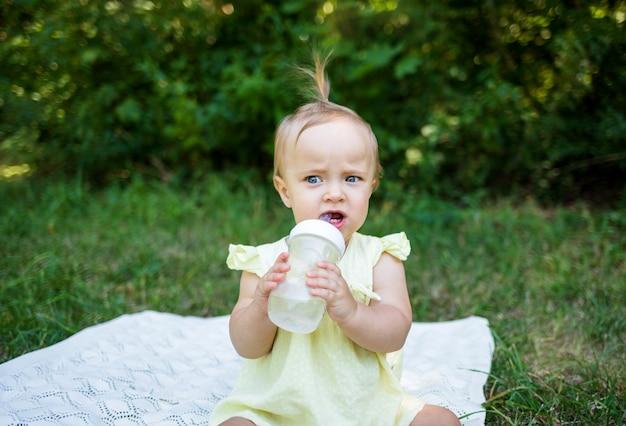 Une petite fille avec une bouteille d'eau assise sur une couverture dans la nature