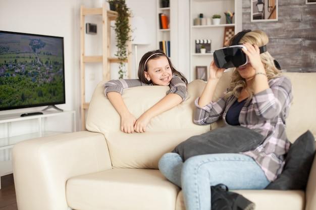 Petite fille à bretelles souriante tandis que sa mère est émerveillée par les lunettes de réalité virtuelle.