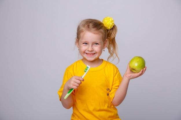 Petite fille avec une brosse à dents, petite fille avec une brosse à dents et une pomme.