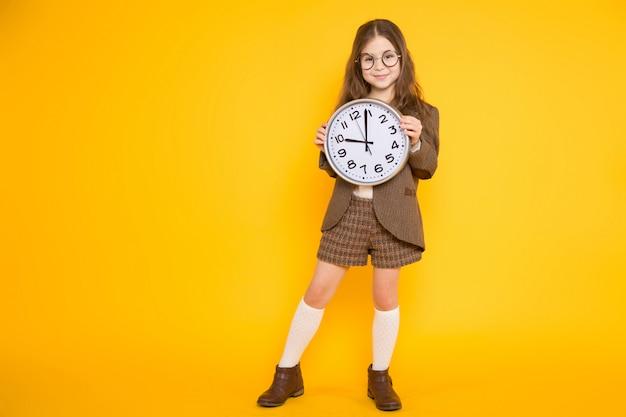 Petite fille brune en costume avec des horloges