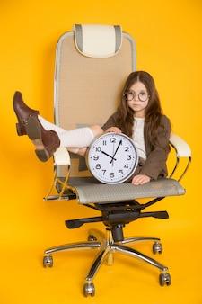 Petite fille brune avec des horloges sur une chaise
