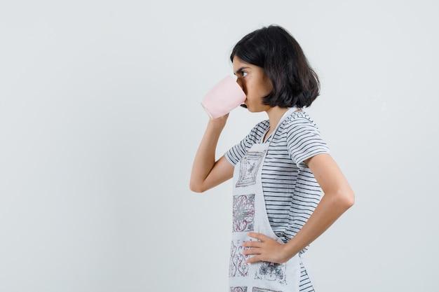 Petite fille buvant du thé aromatique en t-shirt, tablier et à la pensif. .