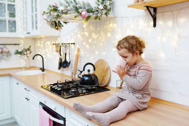 Petite fille buvant du thé assis sur la table dans la cuisine de noël