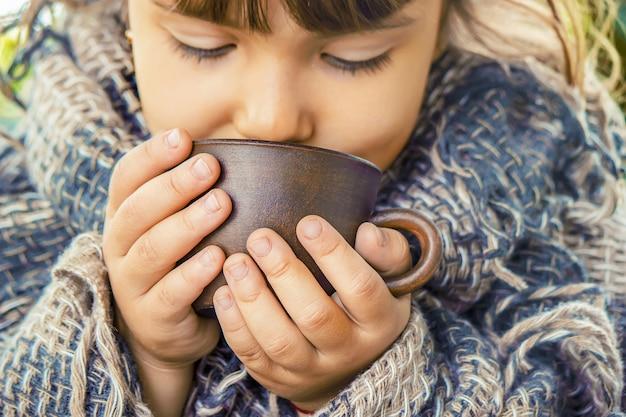 Petite fille buvant du thé. mise au point sélective.