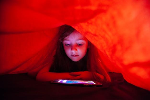 Petite fille cachée à l'aide de la technologie