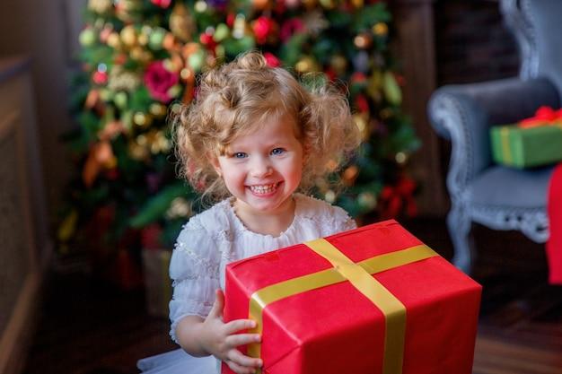 Petite fille avec un cadeau dans ses mains près de l'arbre de noël