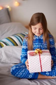 Petite fille avec un cadeau de noël dans le lit