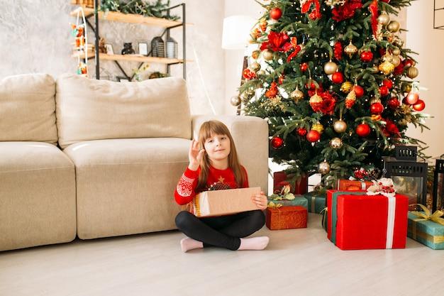 Petite fille avec un cadeau de noël à la maison