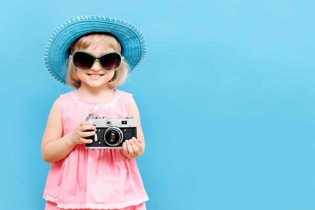 Petite fille avec une caméra à la main dans le studio