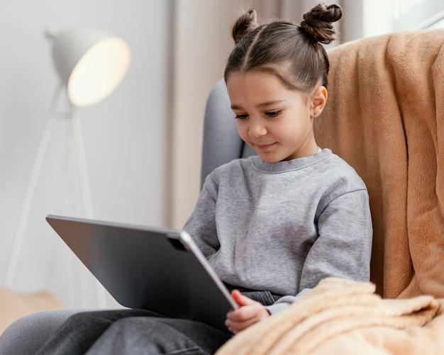 Petite fille sur le canapé à l'aide de tablette