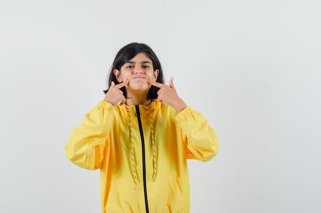 Petite fille à capuche jaune pointant sur son mouh, vue de face.