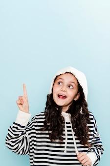 Petite fille avec capuche pointant et copie-espace