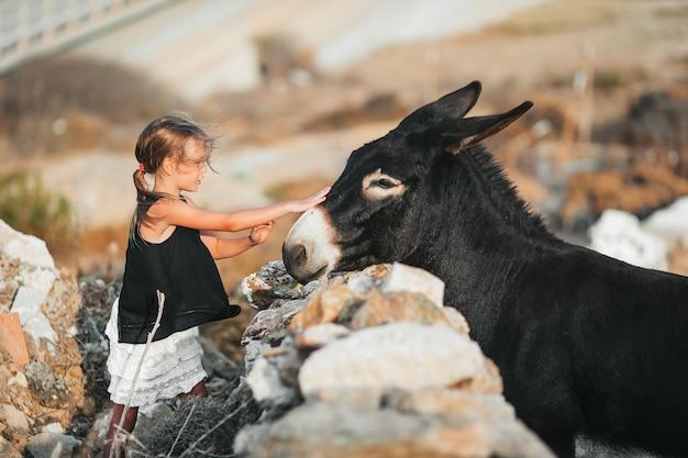Petite fille caressant un âne sur l'île grecque