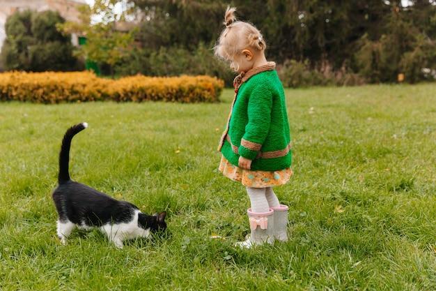 Petite fille caressant un chat noir dans le parc. fille caressant un chat. enfants et animaux.